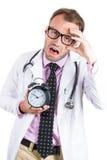 Schläfrige, erschöpfte tragende Gläser männlichen Doktors, die einen Wecker, ermüdet nach einem beschäftigten DA halten stockbild