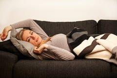 Schläfrige Frau, die auf Sofa stützt Lizenzfreie Stockfotos