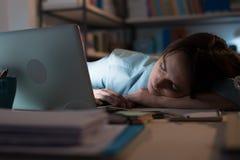 Schläfrige Frau, die mit ihrem Laptop arbeitet stockfotos