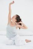 Schläfrige Frau, die oben ihre Arme ausdehnt Lizenzfreies Stockbild