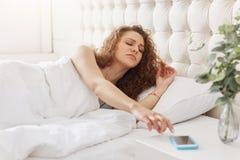 Schläfrige Frau mit dem gelockten Haar stellt Warnung am intelligenten Telefon, wak ab stockfotografie