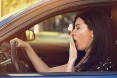 Schläfrige gähnende Frau, die ihr Auto nach Reise der langen Stunde fährt stockfotografie