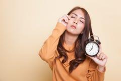 Schläfrige junge Asiatin mit einer Uhr morgens lizenzfreies stockbild