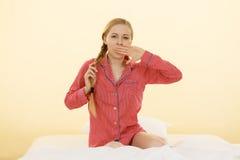 Schläfrige junge Frau, die nette rosa Pyjamas trägt lizenzfreie stockbilder