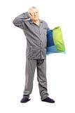 Schläfrige Mitte alterte Mann in den Pyjamas, die ein Kissen halten Stockbild