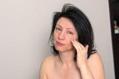 Schläfrige nackte junge Frau mit trüben Augen Lizenzfreies Stockfoto