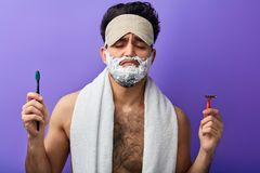 Schläfriger attraktiver gut aussehender Mann mit den geschlossenen Augen, Schaum auf seinem Gesicht rasierend lizenzfreies stockfoto
