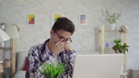 Schläfriger junger asiatischer Mann in einem Hemd, das am Laptop sitzt stock video footage