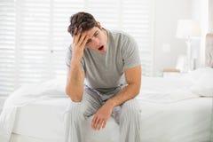 Schläfriger junger Mann, der im Bett sitzt und gähnt Stockfotos