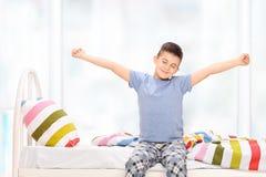 Schläfriger kleiner Junge in den Pyjamas, die sich ausdehnen Stockbilder