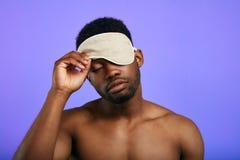 Schläfriger müder Mann, der auf die Schlafenmaske sich entfernt oder sich setzt stockbilder