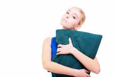Schläfriges blondes Mädchen mit dem grünen Kissen lokalisiert über Weiß Lizenzfreie Stockbilder