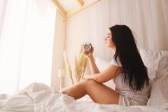 Schl?friges Frauenaufwachen, Wecker abstellend lizenzfreies stockbild