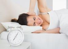 Schläfriges Frauenbedeckungsohr mit der Hand im Bett Stockbilder