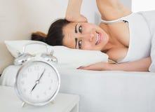 Schläfriges Frauenbedeckungsohr mit der Hand im Bett Lizenzfreie Stockbilder