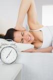 Schläfriges Frauenbedeckungsohr mit der Hand im Bett Lizenzfreies Stockbild