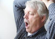 Schläfriges Gegähne des älteren Mannes Stockbild