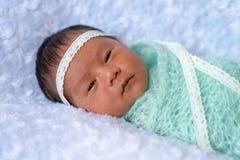 Schläfriges Gesicht neugeborenen Mädchens Ovely legen auf weißer Decke nieder mit hellgrünem Gewebe oben warpping, 6 Tage lizenzfreies stockfoto