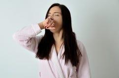 Schläfriges Mädchen im Hausmantel des kleinen Fingers stockbild