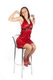 Schläfriges Mädchen im roten Kleid, das auf dem Stuhl sitzt Lizenzfreie Stockfotos