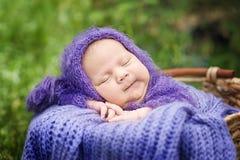 schläft eines-Tag-alt lächelndes neugeborenes Baby 17 auf seinem Magen im Korb auf Natur im Garten im Freien Lizenzfreies Stockbild
