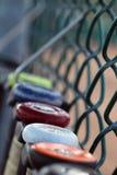 Schläger, die an einem Zaun hängen Lizenzfreie Stockfotos