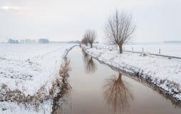 Schlängelnder Abzugsgraben in einer ländlichen Landschaft umfasst mit Schnee Stockbilder