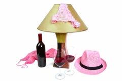 Schlüpfer auf der Lampe nahe der Flasche des Weins und zwei Gläser Stockfotografie