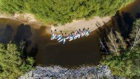 SCHLÜRFEN Sie unidentifizierbaren Leutepaddeleinstieg auf einem ruhigen Fluss während des Sommers Stockfotos