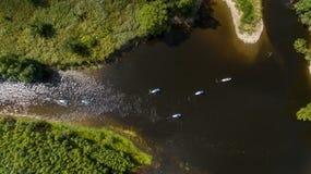 SCHLÜRFEN Sie unidentifizierbaren Leutepaddeleinstieg auf einem ruhigen Fluss während des Sommers Lizenzfreie Stockbilder