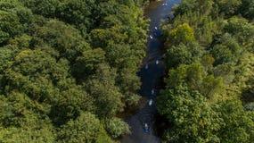 SCHLÜRFEN Sie unidentifizierbaren Leutepaddeleinstieg auf einem ruhigen Fluss während des Sommers Stockbild