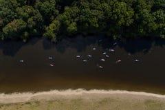 SCHLÜRFEN Sie unidentifizierbaren Leutepaddeleinstieg auf einem ruhigen Fluss während des Sommers Stockfotografie