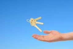 Schlüssel in der Hand über Himmelhintergrund Lizenzfreies Stockfoto