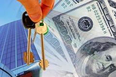 Schlüssel gegen die Fassade des Bürogebäudes und des Geldes Stockbild