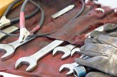 Schlüssel, Handschuhe und Werkzeuge auf Machanic-Tabelle stockfotos