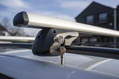 Schlüssel im Verschluss befestigen den Halter für den Autokofferraum- oder Frachtkasten am Fahrzeugdach, an einem sonnigen Frühli lizenzfreie stockfotografie