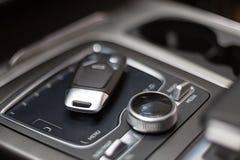Schlüssel liegt im Auto auf der Fingerspitzentablettsteuerung Erstklassiges Auto des Salons mit keyless Zugang lizenzfreies stockfoto