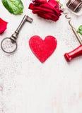 Schlüssel, rotes Herz, rosafarben und Schokolade auf weißem Holztisch, Liebeshintergrund Stockbild