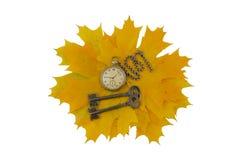 Schlüssel und alte Taschenuhr auf gelbe Blätter Lizenzfreie Stockfotografie