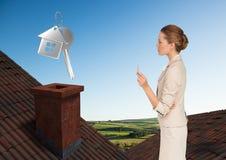 Schlüssel und Geschäftsfrau des Haus-3D, die auf Dächern mit Kamin und grüner Landlandschaft stehen Stockfotografie