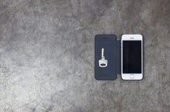 Schlüssel und Handy auf Metallhintergrund Lizenzfreies Stockbild