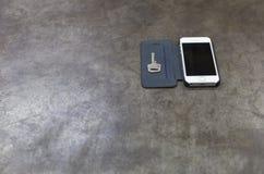 Schlüssel und Handy auf Metallhintergrund Stockbild