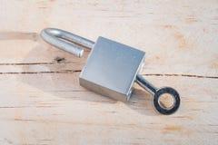 Schlüssel und Verschluss auf hölzernem Hintergrund Stockfotografie