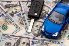 Schlüssel zum Auto und zum Auto, die auf 100 Dollar liegen Stockfotografie