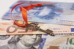Schlüssel zum Erfolg mit rotem Bogen auf amerikanischen Dollar, europäischer Euro, S Lizenzfreies Stockbild