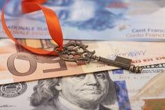 Schlüssel zum Erfolg mit rotem Bogen auf amerikanischen Dollar, europäischer Euro, S Lizenzfreies Stockfoto