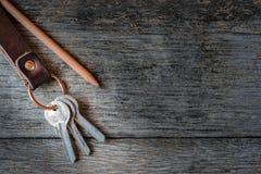 Schlüsselanhänger und Bleistift auf hölzernem Hintergrund Stockbild