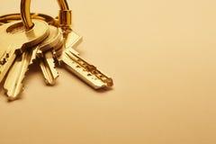 Schlüsselring mit Schlüsseln im goldenen Ton über einem leeren Hintergrund Lizenzfreies Stockfoto
