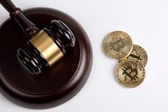 Schlüsselwährung, goldenes bitcoin mit einem hölzernen Richterhammer auf weißem Hintergrund stockbild