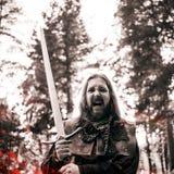 Schlachtruf, Kampf Adeln Sie im Waldkerl im mittelalterlichen Kostüm mit Klinge Effekt des Feuers und des Tonens Lizenzfreie Stockfotografie